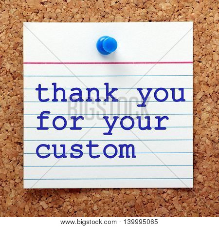 The words Thank You For Your Custom in blue text on a note card pinned to a cork notice board as a reminder of good customer service