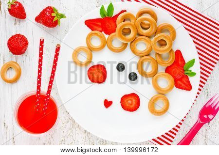 Funny food art idea for healthy baby girl breakfast - bagels with berry in the form of smiling face. Picture on a plate fun with food concept