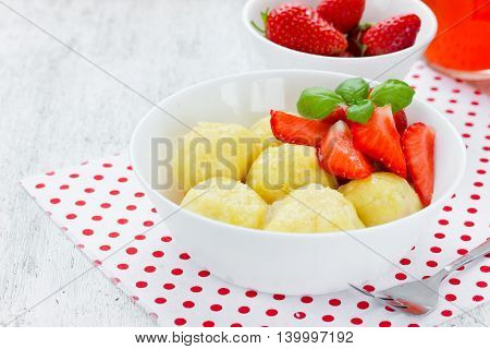 Healthy dessert - dumplings with cheese and strawberry on white table blank space for text selective focus