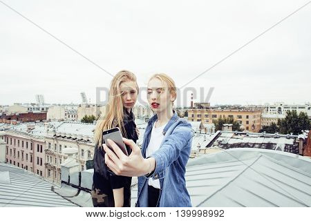 two cool blond real girls friends making selfie on roof top, lifestyle people concept, modern teens