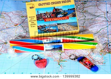 WEYMOUTH, UNITED KINGDOM - JULY 24, 2016 - Box of clotted cream fudge with sticks of rock and keyrings on a map Weymouth Dorset England UK Western Europe, July 24, 2016.