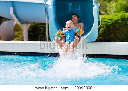 Happy boys two brothers having fun together on water slide in a swimming pool during summer vacation in a beautiful tropical resort. Children sliding and playing in aqua park.