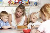 stock photo of montessori school  - Adult Helping Young Children at Montessori - JPG