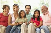 stock photo of extended family  - Extended Family Relaxing On Sofa At Home Together - JPG