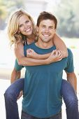 stock photo of young men  - Young Man Giving Woman Piggyback Outdoors - JPG