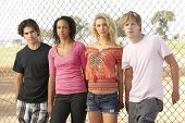 stock photo of male female  - Diverse Group Of Teenagers Standing In Playground - JPG