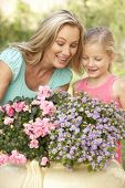 Woman With Daughter Gardening Together