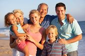 stock photo of shoreline  - Portrait Of Three Generation Family On Beach Holiday - JPG