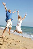Постер, плакат: Старший пара наслаждаясь пляжного отдыха прыжки в воздухе