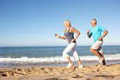 stock photo of older men  - Senior Couple In Fitness Clothing Running Along Beach - JPG