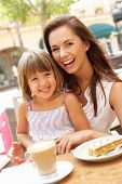 stock photo of mother child  - Mother And Daughter Enjoying Cup Of Coffee And Piece Of Cake In Cafe - JPG