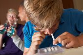 stock photo of underage  - Group Of Teenage Boys Taking Drugs At Home - JPG