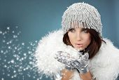 stock photo of hottie  - Attracive girl in santa cloth blowing snow from hands - JPG