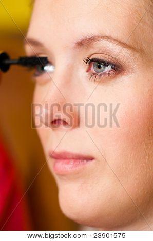 woman is applying mascara