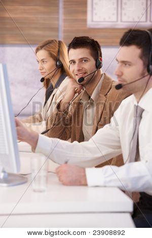 Happy young dispatcher working in callcenter, smiling.?