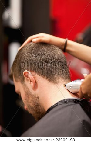 Portrait of a male young student having a haircut with a hair clippers