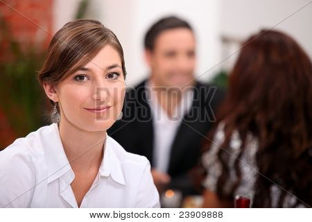 Focus on a woman sitting in a restaurant with other diners in the background
