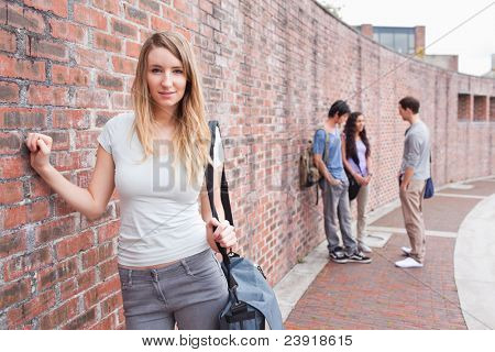Cute student posing while her friends are talking outside a building