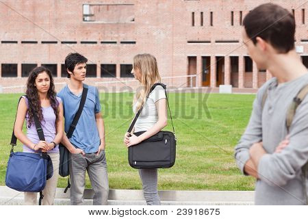 Student looking at one of his classmates talking outside a building