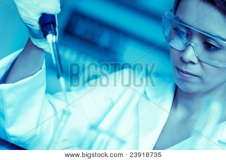 Science student dropping liquid in a test tube in a laboratory