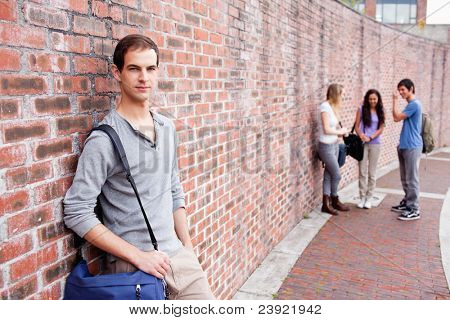 Student leaning on a wall while his friends are talking outside a building