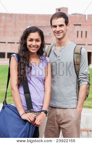 Portrait of a smiling student couple posing outside building