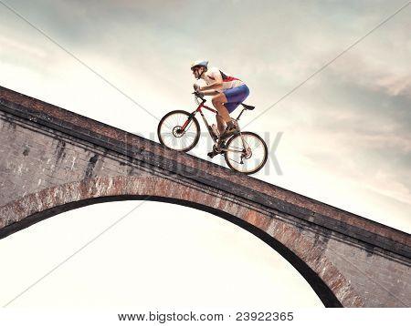 Cyclist riding bike on a bridge