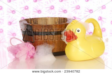 wooden wash tub and rubber duck with soap suds
