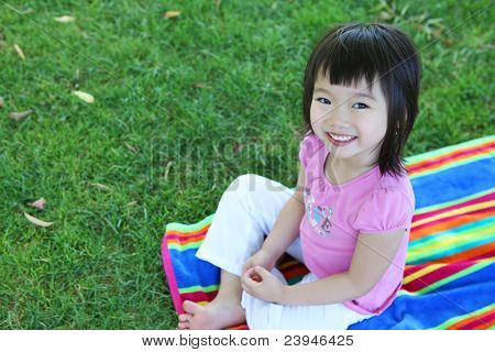 A cute young asian girl sitting on a rainbow colored towel on the grass