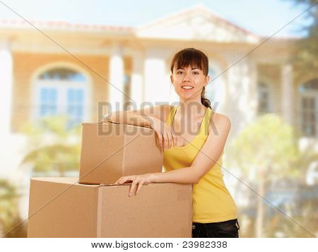 Portrait of young girl with boxes moving to a new home outside background