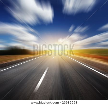Motion blurred asphalt road and blue sky with blurred clouds