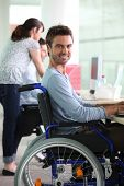 stock photo of people work  - Man in wheelchair at work - JPG