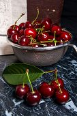 Several Red Sweet Cherries And Big Green Leaf On The Table. Fresh Organic Cherry In Colander On Dark poster