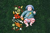 Baby In Colorful Clothes Trying Food And Frame Of Different Fresh Fruits And Vegetables On Green Gra poster