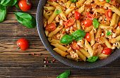 Penne Pasta In Tomato Sauce With Chicken, Tomatoes, Decorated With Basil On A Wooden Table. Italian  poster