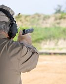 image of shooting-range  - Man using a semi automatic pistol at the shooting range - JPG