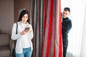 Woman using phone, killer hiding behind a curtain poster