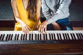 Piano teacher giving lessons to his student in music school  poster