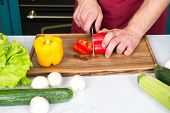 Vegetables Getting Cut On Wooden Cutting Board. Hand Slice Pepper With Ceramic Knife. Food Preparati poster