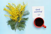 Good Morning Wishes, Coffee Cup And Flowers Of Mimosa On Blue Table poster