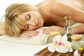stock photo of massage oil  - Beautiful young woman enjoying massage at spa salon - JPG