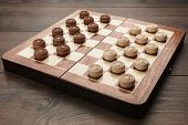 Wooden Draughts Game. Draughts On Brown Table. Wooden Draughts Ready For A Game. Classical Draughts  poster