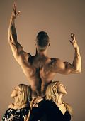 Man Bodybuilder With Muscular Back Raise Hands Biceps, Triceps, And Girls Or Women With Long Blond H poster