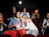 stock photo of watching movie  - Young scared couple at the movie theater - JPG