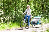Mother On Bicycle With Baby Bike Trailer In Park poster