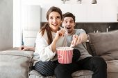 Portrait of an excited young couple relaxing on a couch at home while watching TV and eating popcorn poster