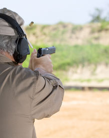 stock photo of shooting-range  - Man using a semi automatic pistol at the shooting range - JPG