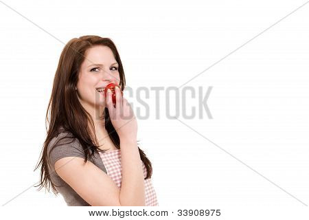 happy young woman about to eat a tomato