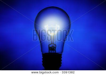 Un-Lit Light Bulb Against Blue Background