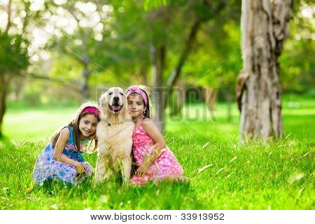 Two young girls hugging golden retriever dog in the park
